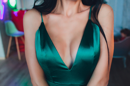 neckline, beautiful large female breast, green dress, close-up