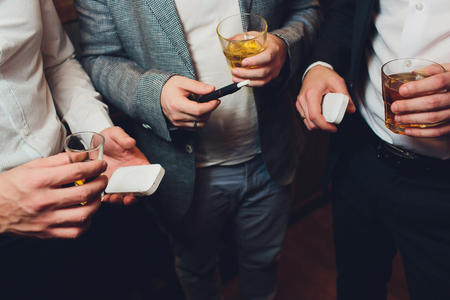 A heat-not-burn tobacco product technology.Man holding in one hand smoking module before smoking. three men are holding alcohol, the concept of smoking electronic cigarettes in the room