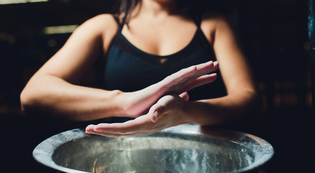 Cropped shot of young female athlete clapping hands with chalk powder before strength training
