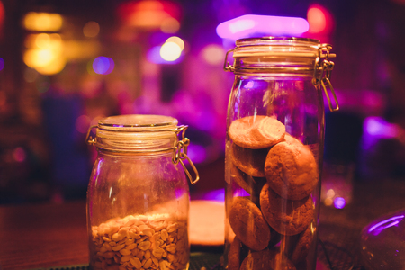 Desserts choice. Cookies and biscuits in glass jars on counter bar for sale. Chocolate drops and chips, oatmeal cookies stacks