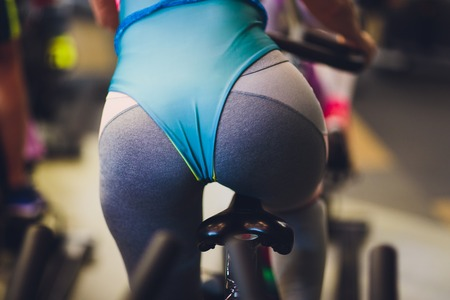 Beautiful young woman in a gym female on bicycle fanny Imagens