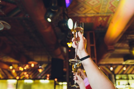 Celebration. Hands holding the glasses of champagne and wine making a toast. Shallow DOF