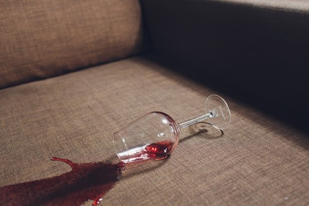 Red wine spilled on a grey couch sofa