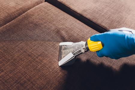 Bank chemische reiniging met professionele extractiemethode. Gestoffeerde meubels. Vroege voorjaarsschoonmaak of regelmatige schoonmaak. Stomerij in lichtblauwe beschermende handschoen medewerker die vuil van meubels in flat verwijdert