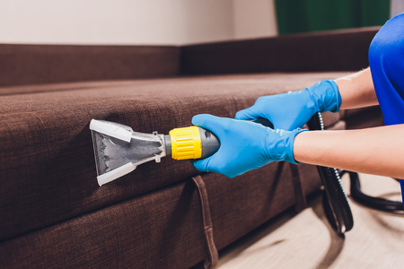 Sofa chemical cleaning with professionally extraction method. Upholstered furniture. Early spring cleaning or regular clean up. Dry cleaner's in light blue protective glove employee removing dirt from furniture in flat