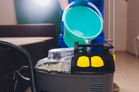 Professional equipment for dry cleaning. chemistry, extractor, pours water inside man in colored uniform, workwear Stockfoto