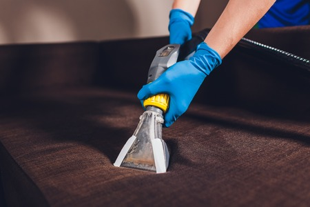 Sofa chemical cleaning with professionally extraction method. Upholstered furniture. Early spring cleaning or regular clean up. Dry cleaners in protective glove employee removing dirt from furniture in flat