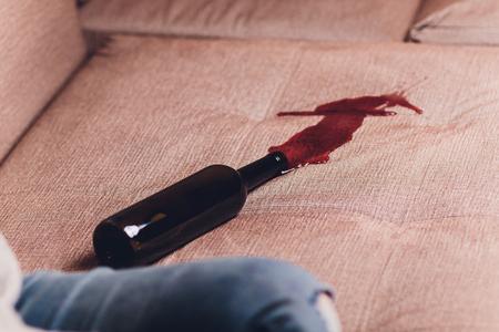 Vin rouge renversé sur un canapé marron foncé bouteille de vin rouge a chuté