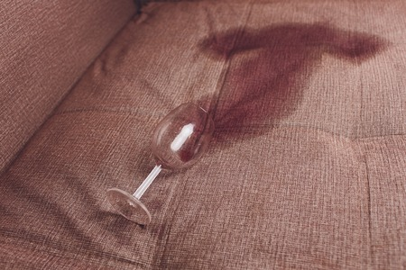 Red wine spilled on a brown couch sofa