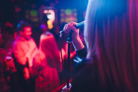 Unterhaltung bei einer Hochzeit. Eine Sängerin interagiert mit der Menge, während ein Mann eine Akustikgitarre spielt. Standard-Bild