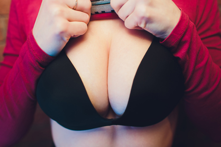 Sexy big breast. Female black bra lingerie. Sexiness and sensuality. Young attractive woman, seductive lady, chest in black brassiere. Female seductive breast of large size after surgery. Sexy volume