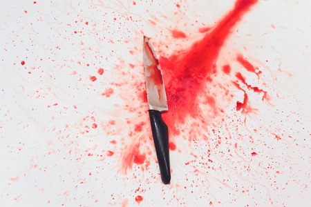 Closeup of bloody knife with splattered blood in the sink. Concept of Halloween horror Standard-Bild