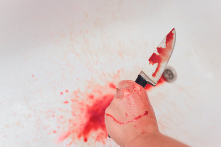 Halloween horror concept. Image of unknown woman hands holding a knife with bloody stain in the sink Standard-Bild - 120584690
