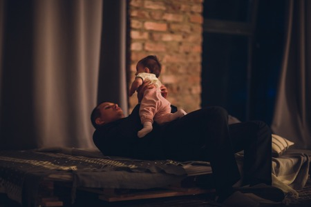happy young father and his baby, against dark studio background Imagens