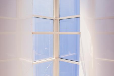 Un moderno tragaluz abuhardillado en una habitación del ático contra el cielo azul