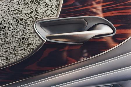 Car inside. Interior of prestige modern car. Climate control, hi-end sound speakers, seat memory, door lever side mirror. White cockpit with wood metal decoration blue ambient light Banco de Imagens