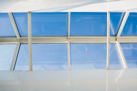 A modern open skylight mansard window in an attic room against blue sky Reklamní fotografie