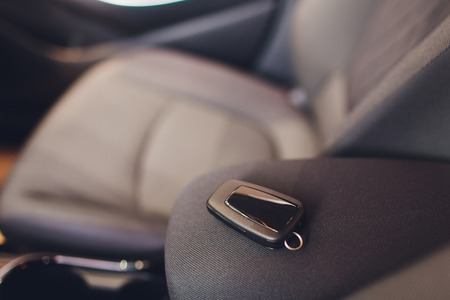 Gros plan à l'intérieur du véhicule de l'allumage par clé sans fil. Clé de démarrage du moteur. Télécommande de clé de voiture dans un intérieur en cuir perforé noir. Fond de voiture moderne. Voiture moderne Détails intérieurs. Détaillant de voiture. Les clés se bouchent