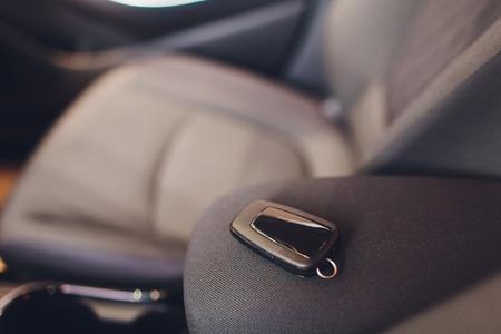 Nahaufnahme innerhalb des Fahrzeugs der drahtlosen Schlüsselzündung. Motorschlüssel starten. Autoschlüssel-Fernbedienung in schwarzem perforiertem Leder. Moderner Autohintergrund. Modernes Auto Innendetails. Professionelle Autopflege. Schlüssel hautnah