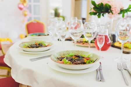 Elegante mesa de banquete preparada para conferencia o fiesta y flores decoradas para invitados