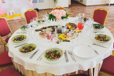 Elegant banquet table prepared for conference or party and decorated flowers for guests