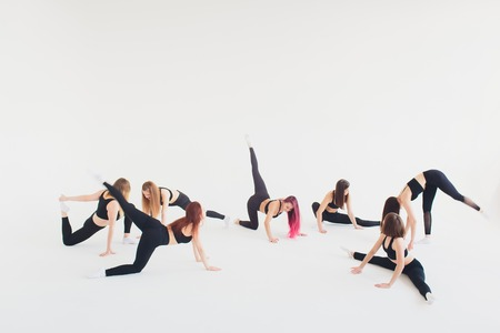 Fitness, stretching practice, group of two attractive happy smiling fit mature women working out in sports club, doing Extended Side Angle posture, utthita parshvakonasana pose in class, full length.