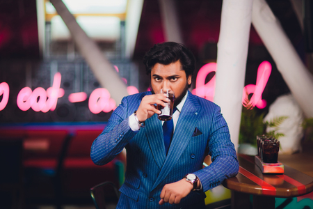 Handsome young man drinking cocktail at bar counter, wearing business suit.