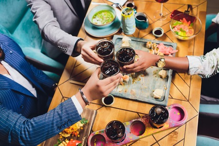 Hands of friends together in circle holding the different cocktails with ice on background of the old wooden table surface. View from top.