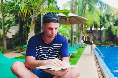 A man reading book beside swimming pool in the garden.