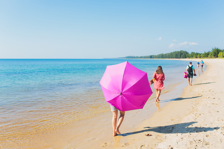 Girl with an orange umbrella on the sandy beach. Stock Photo