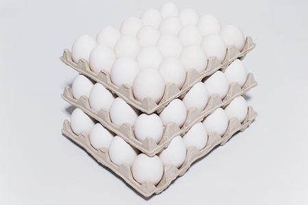 White eggs of a hen in harmless, cardboard packing on a white background. 3 packs.