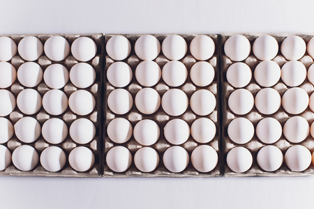 White eggs of a hen in harmless, cardboard packing on a white background. Stock fotó
