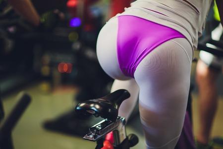 Belle jeune femme dans une salle de gym femelle à vélo. chatte Banque d'images
