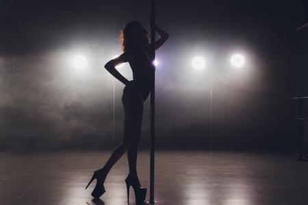 junge Striptease-Tänzerin, die sich in High Heels auf der Bühne im Strip-Nachtclub bewegt, Pole Dance.