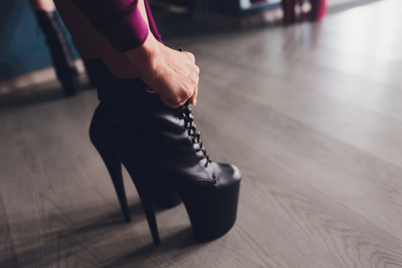 Woman puts on shoes and dance on pole studio
