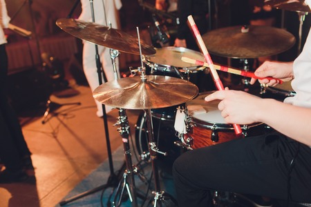 Drummer with a drumsticks in his hands playing on drum set on stage on the black background. Stock Photo