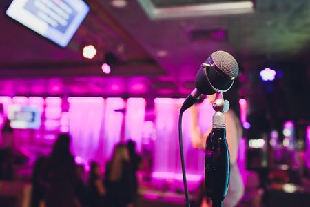 Micrófono retro contra desenfoque de luz colorida en pub y restaurante de fondo.