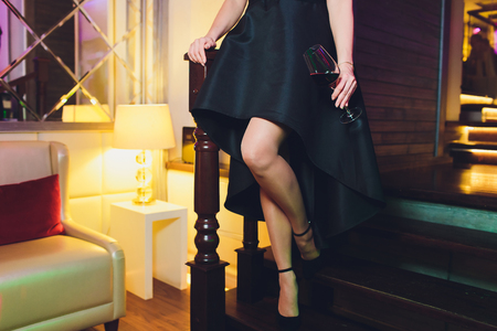 Perfect female legs wearing high heels and black dress. Reklamní fotografie