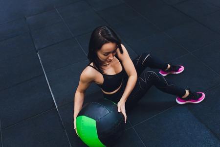 Femme musclée faisant un entraînement de base intense dans une salle de sport. Femme forte faisant des exercices de base sur un tapis de fitness avec ballon de médecine dans un club de santé.