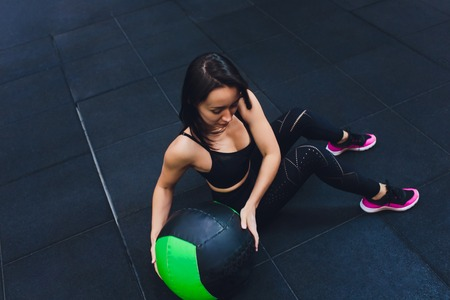 Muscular woman doing intense core workout in gym. Strong female doing core exercise on fitness mat with medicine ball in health club. Banco de Imagens
