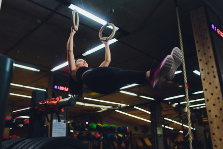 Young athletic sportswoman exercising on gymnastic rings at gym