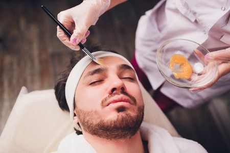 Unshaven man having cosmetic mask in spa salon, top view.