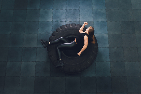 Powerful, attractive muscular girl engaged in gym, training with giant tires in the gym. Athlete resting after a hard workout. Exercise with heavy weight in the gym.