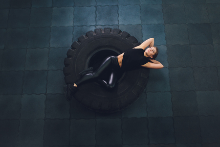 Powerful, attractive muscular girl engaged in gym, training with giant tires in the gym. Athlete resting after a hard workout. Exercise with heavy weight in the gym. Stockfoto