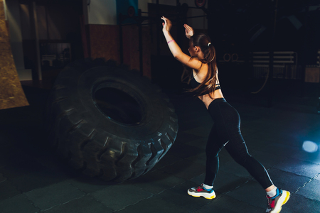 Fitness woman flipping wheel tire in gym. Fit female athlete working out with a huge tire. Back view. Sportswoman doing an strength exercise training. Stock Photo