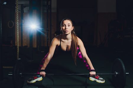 a beautiful sports girl trains a bicep with a rod in her hands in the gym.