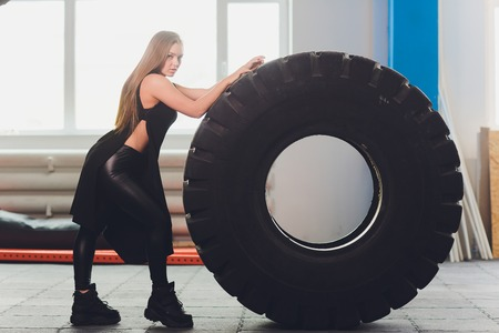 Fit female athlete working out with a huge tire, turning and carry in the gym. woman exercising with big tire.