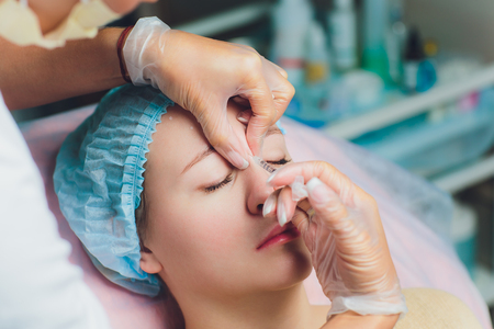 Doctor giving face lifting injection on mid age woman in the forehead between eyebrows to remove expression wrinkles in a clinic surgery room O.R background Beautify filler for face anti aging concept. Stok Fotoğraf