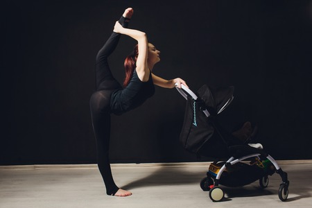 young slim mother with a pram. young mother raises her leg, acrobatics, gymnastics, sports.