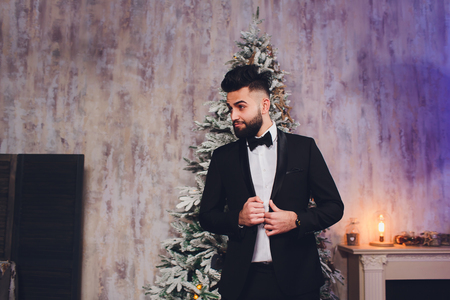 Handsome bearded businessman in classic suit. Mens beauty, fashion. Male in suit, man in tuxedo, stylish in a cloth jacket.